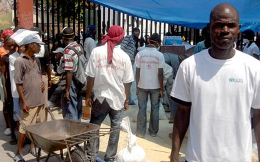 Haitian Coast Guard officer Jean Raynold Bataille, right, one of the community leaders who worked with the Marines in Carrefour, supervised this food distribution point in the city on Wednesday.