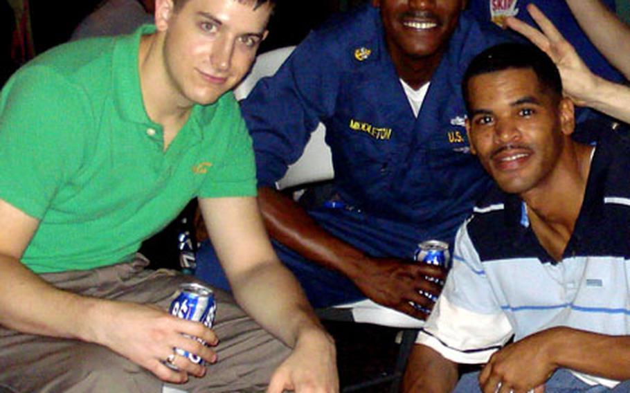 Petty Officer 1st Class Patrick Brendan Mack, left, and Seaman Lonnie Davis Jr. with friends.