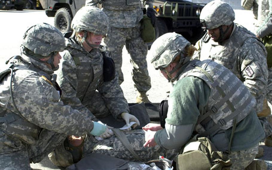 Medics simulate treatment of battlefield injuries Tuesday during an exercise that brought some 200 medical personnel from seven companies to Camp Stanley in South Korea. During the exercise, the medical units practiced procedures that would be used in the event hostilities resumed on the peninsula.