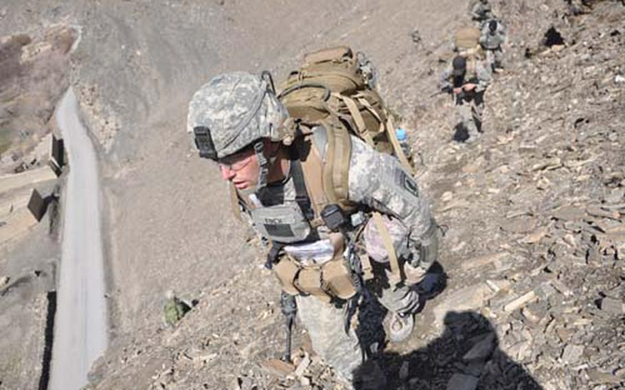 First Lt. Michael Finch scales a steep hillside during a patrol, leading his platoon from ridgeline to ridgeline to avoid booby traps in the farmland below.