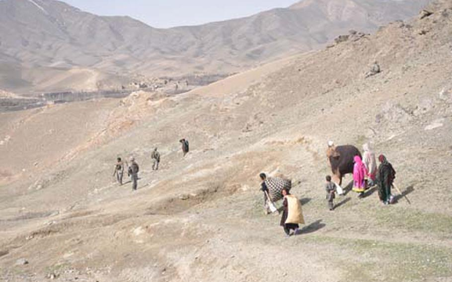 Villagers walk by a patrol of U.S. and Afghan soldiers in the hills above Wardak province's Tangi Valley.