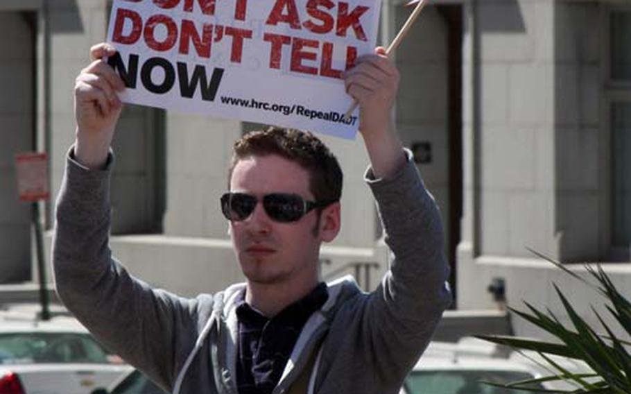 """A protestor cheers on calls for a repeal of the military's """"don't ask, don't tell"""" law ."""