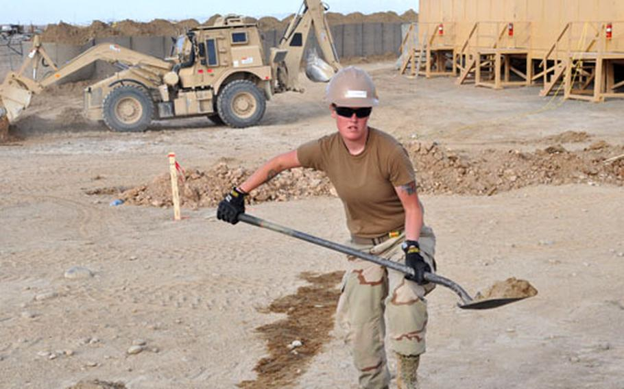 Constructionman McKenzie Dupons, 20, a Navy Seabee, carries dirt to fill in the frame for a concrete floor where she works at the construction site at Forward Operating Base Sharana.