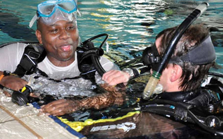 Staff Sgt. Derrick McClam jokes with his instructor after struggling to keep water out of his mask during a scuba diving class for wounded soldiers in Bamberg, Germany.