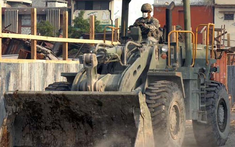 A U.S. soldier, wearing a mask to protect him from dust, clears earthquake rubble from Port-au-Prince in late February.