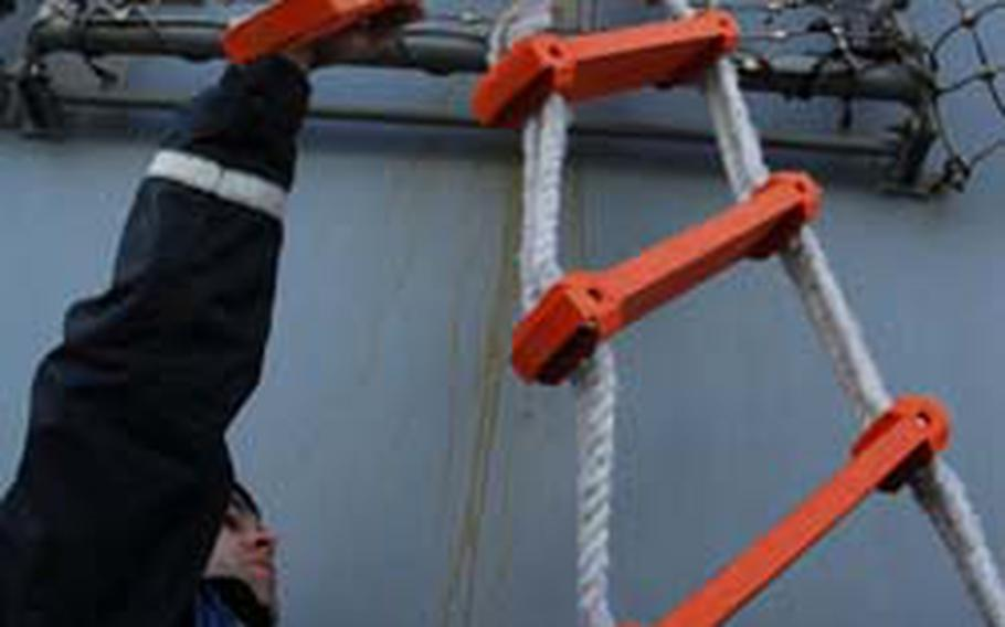 Sailors on the USS Curtis Wilbur on Saturday drop a ladder to passengers waiting below.