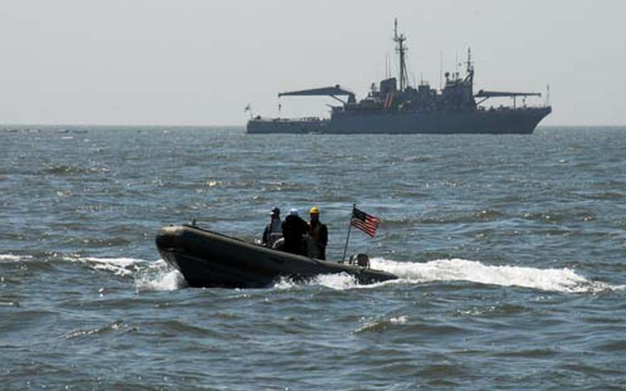 U.S. Navy personnel in a Rigid Inflatable Boat check the waters near a South Korean salvage ship, in the background, Saturday at the site of the wreckage of the South Korea patrol ship Cheonan, which sank on March 26 after an explosion.