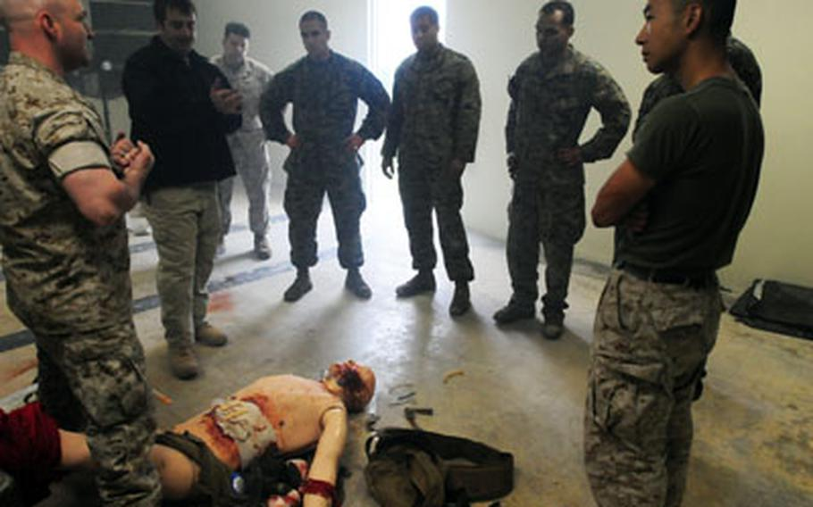 Petty Officer 1st Class Jeremy Dunlap (left) and retired Navy Corpsman Mark Kane (second from left) briefs Marines and sailors from Special Operation Training Group after they finished treating a manikin during a medical simulation scenario.
