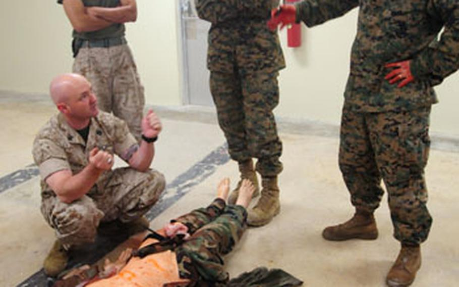 Petty Officer 1st Class Jeremy Dunlap (left) briefs Marines and sailors from Special Operation Training Group after they finished treating a mannequin during a medical simulation scenario. The mannequins are able to replicate real life responses.