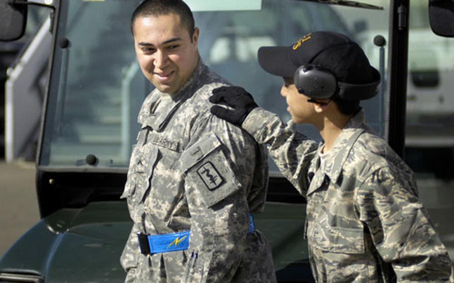 Cresencio Santos, 15, gives his older brother, Army Pvt. Kevin Colindres, a loving slap on the shoulder during a visit Tuesday to Ramstein Air Base's flightline.