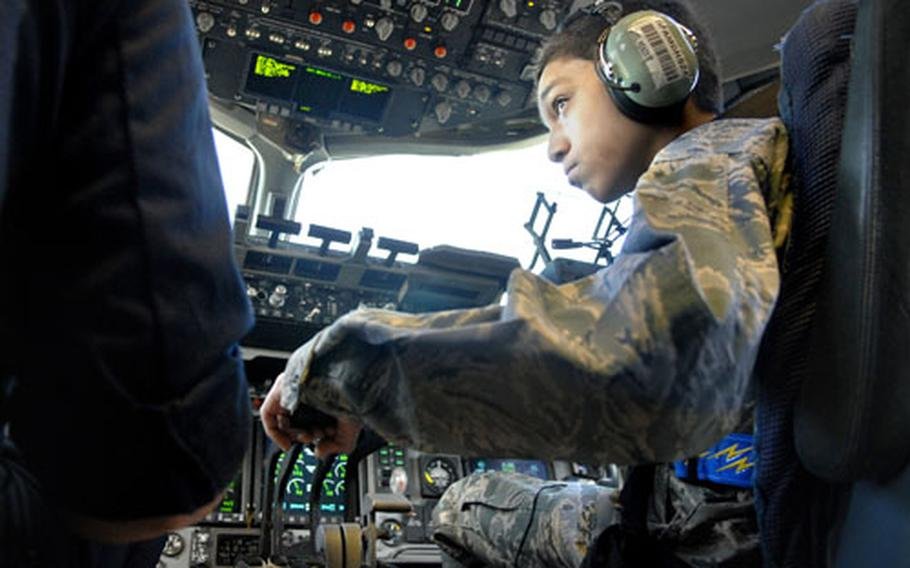 Cresencio Santos looks up at Air Force Staff Sgt. Chris Pugh, a crew chief with the 721st Aircraft Maintenance Squadron, as he adjusts the throttles on a C-17 cargo aircraft during a live engine run-up Tuesday at Ramstein Air Base.