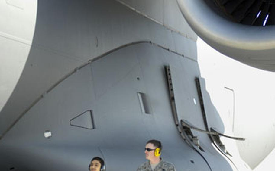 """Cresencio Santos and Air Force Staff Sgt. Donald Ray, an airman from the 721st Aerial Port Squadron, do a """"walk-around"""" on a C-17 cargo aircraft before loading cargo bound for Japan Tuesday at Ramstein Air Base."""
