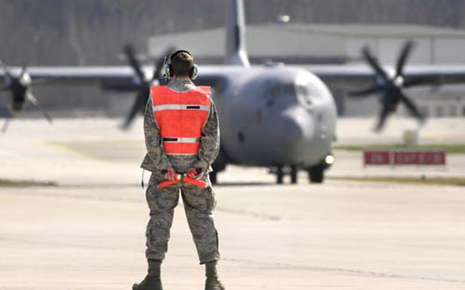 Airman 1st Class Paul Driscoll, a hydraulics specialist, readies to direct in a C-130J on Ramstein Air Base's flight line in April 2009 .