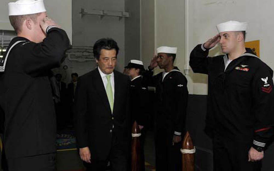 Japanese Foreign Minister Katsuya Okada is greeted by U.S. sailors during a visit Saturday to the aircraft carrier USS George Washington at Yokosuka Naval Base, Japan.