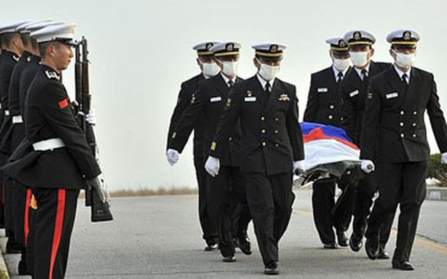 Navy personnel carry the one of the body of the 46 missing sailors of the sunken South Korean naval ship Cheonan, at the naval port in Pyeongtaek, south of Seoul, South Korea, Thursday, April 15, 2010.