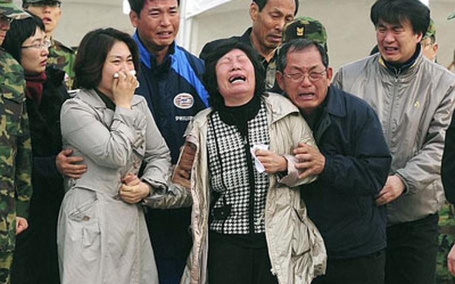 Family members of Petty Officer 1st class Lee Sang-joon cry as Navy personnel carry his body, one of the 46 missing sailors of the sunken South Korean naval ship Cheonan.