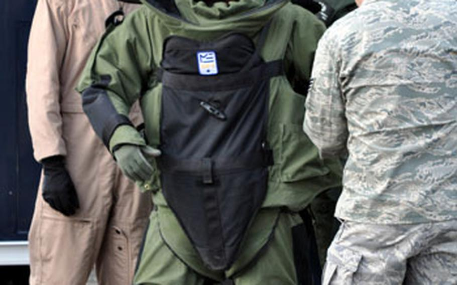Fellow EOD technicians help Staff Sgt. Michael Overton into his bomb protection suit.