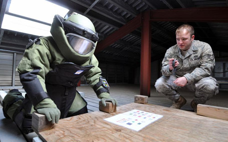 Staff Sgt. Anthony Walling, right, gives Staff Sgt. Michael Overton 60 seconds to memorize as many symbols as he can from a piece of paper during a training and conditioning drill. Overton had already climbed the three-story building's stairs twice wearing the 70-pound bomb protection suit before attempting to memorized the symbols.