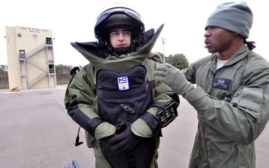 Staff Sgt. Michael Overton, right, helps Airman 1st Class Jason Wayne into his 70-pound bomb protection suit for a timed conditioning and familiarity drill on Thursday at Misawa Air Base, Japan.