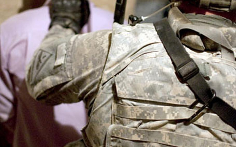 A U.S. soldier keeps control over a man arrested by Iraqi police after they obtained a video of him preparing to fire a rocket on a U.S. base. The police said they believed the man was a member of al-Qaida.