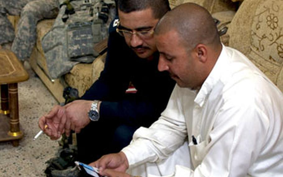 Iraqi police Sgt. Maj. Jassim Mohammed Ali al-Tikriti, right, and Major Bashar Fouad Younis Mohammed look at images on a cell phone as they plan a raid in Hawijah. U.S. Army Staff Sgt. James Davis waits in the background.