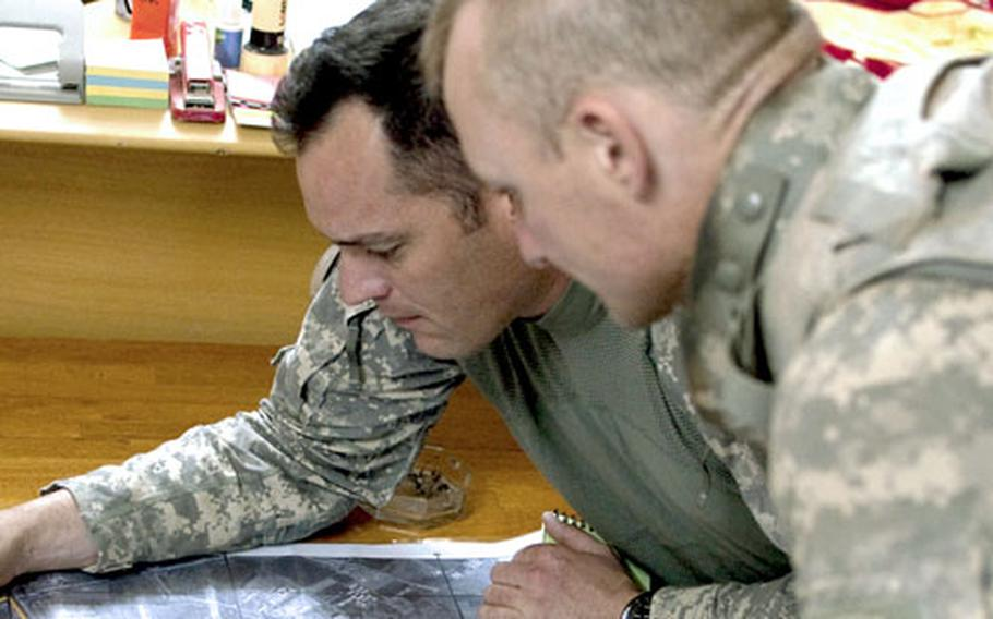 U.S. Army Capt. Scott Wares, left, and Staff Sgt. James Davis plan a route for a raid to be conducted with Iraqi police in the northern town of Hawijah.
