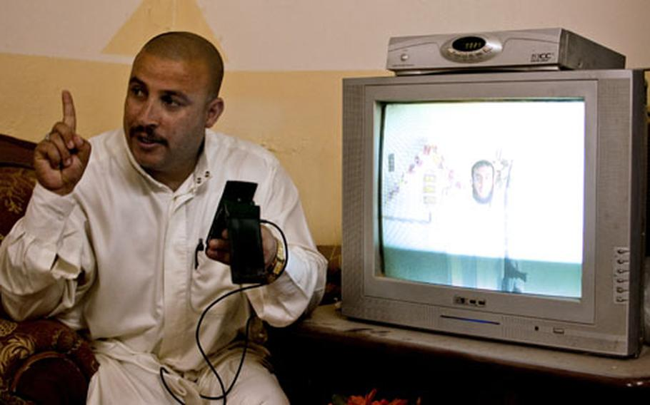 Iraqi Police Sgt. Maj. Jassim Mohammed Ali al-Tikriti shows American troops a cell phone video of a man apparently preparing to fire a rocket at a nearby U.S. base. Though violence has dropped precipitously in this one-time insurgent stronghold, the American base, FOB McHenry, takes incoming fire once or twice a week.