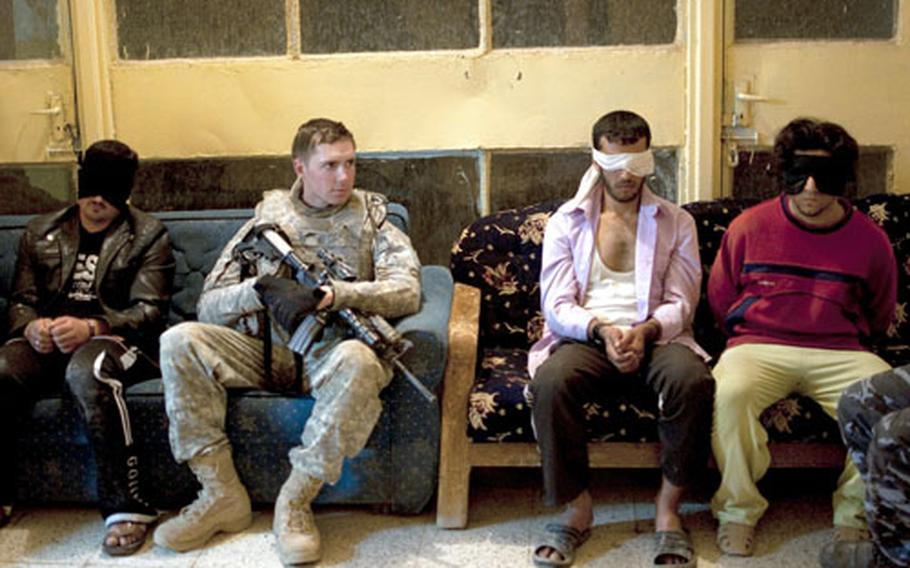 Men arrested during a joint raid in Hawijah sit in the lobby of the local police station. The man at far right, picked up after cutting off a police officer in traffic, was later released.