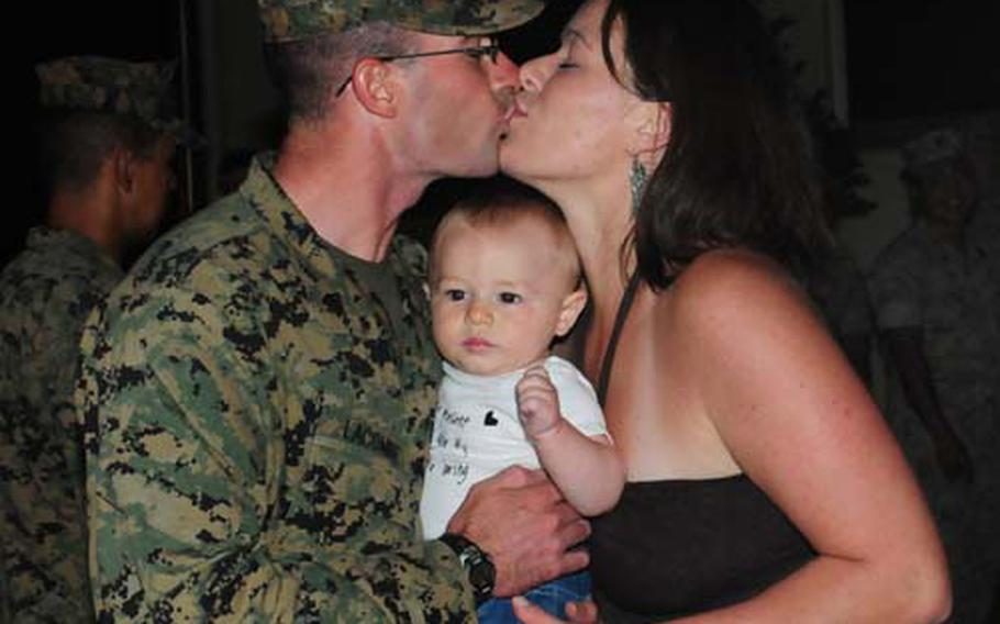 Sgt. Thomas Lacombe, a Marine from Currie, N.C., kisses his wife, Martha, after returning Wednesday to Camp Schwab, Okinawa, after a nine-month deployment in Afghanistan. Lacombe, 27, holds his son, Aaron, who was only 9 days old when the sergeant deployed.
