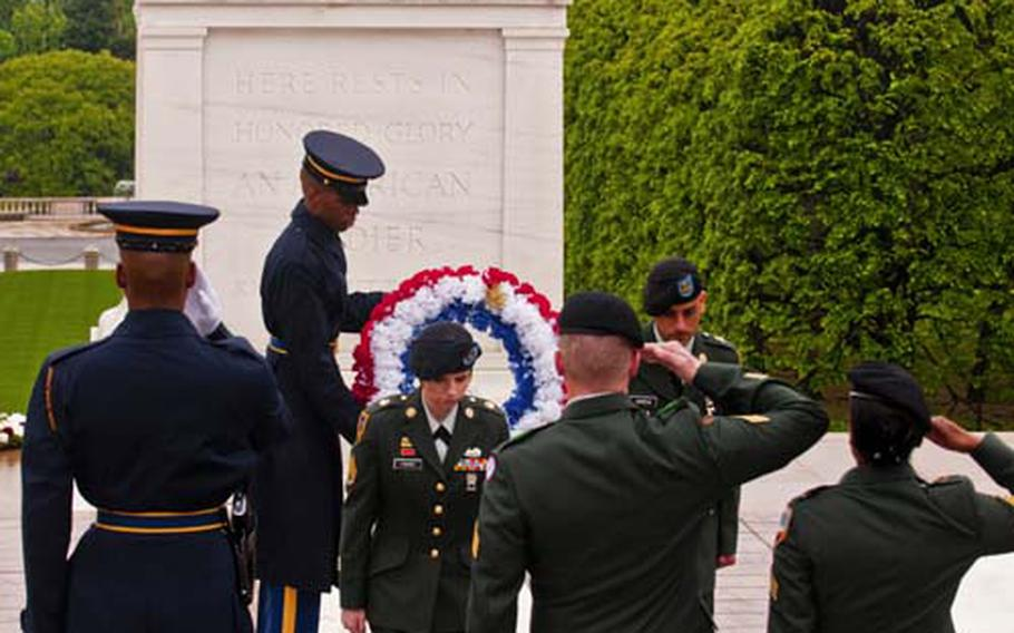 Staff Sgt. Courteney J. Fisher, center, and Specialist Tomas Garcia, far right, return to formation after laying a wreath at the Tomb of the Unknowns in at Arlington National Cemetery on Wednesday.