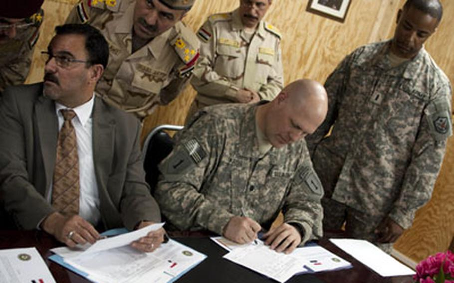 U.S. Army Lt. Col. Paul Kreis, center, and Samir al-Haddad, an official from the office of the Iraqi prime minister, sign papers transferring Forward Operating Base Summerall from U.S. to Iraqi control. Iraqi Army Brig. Gen. Abdullah al-Dulawe, third from left, and U.S. Army Chief Warrant Officer Kenneth Shuler, right, look on.
