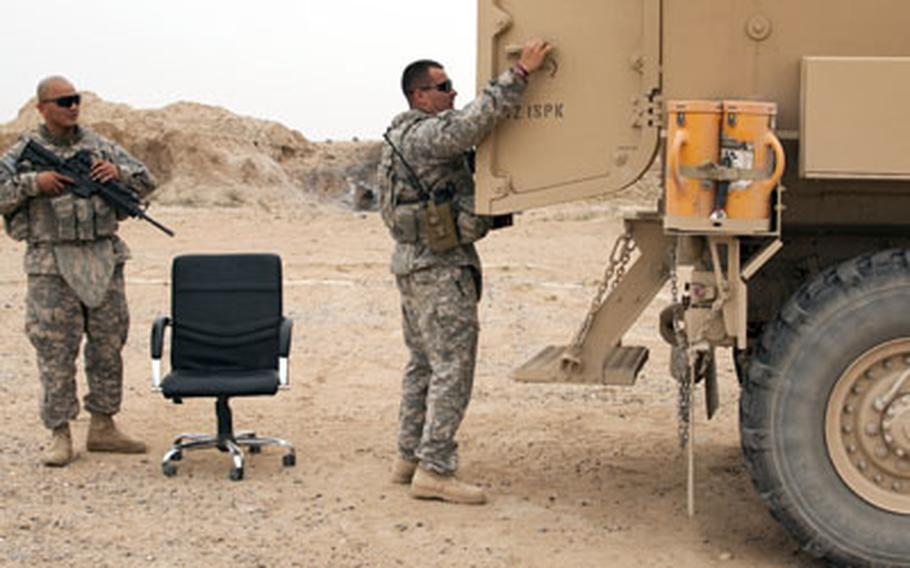 U.S. soldiers prepare to load a favorite desk chair into the back of a Mine Resistant Ambush Protected vehicle before departing Forward Operating Base Summerall near Beiji, Iraq.