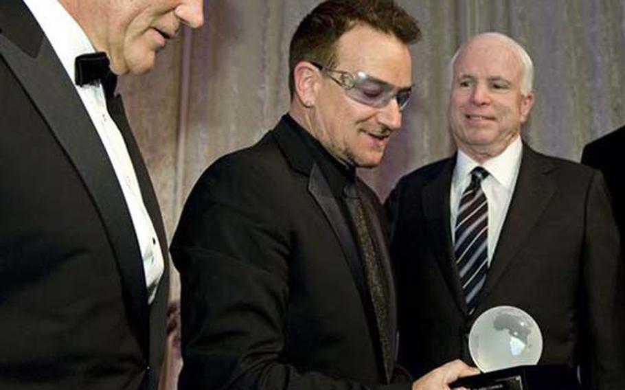 Bono, center, is presented with the award for international humanitarian leadership by former Sen. Chuck Hagel, R-Neb., left, Sen. John McCain, R-Ariz., during the Atlantic Council annual awards dinner in Washington, Wednesday, April 28, 2010.