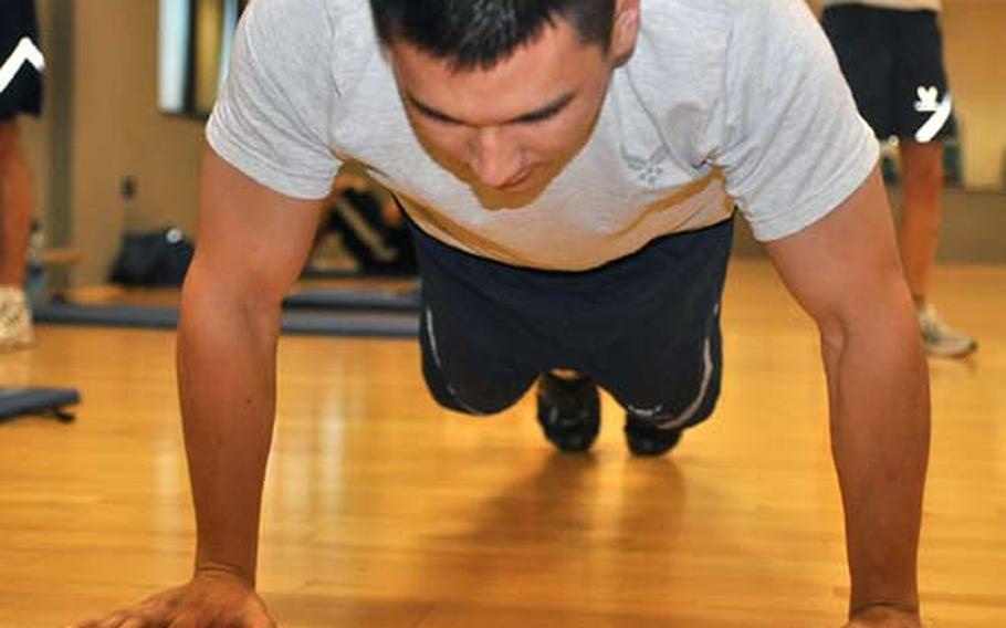 Senior Airman Anthony Enomoto does push-ups Friday at the Dragon Fitness Center at Aviano Air Base, Italy, during physical fitness testing. Enomoto and other members of the 31st Operations Support Squadron appeared to be doing well in the testing. But samples taken by the Air Force indicate that many airmen worldwide will have to improve their fitness to pass new standards that take effect July 1.