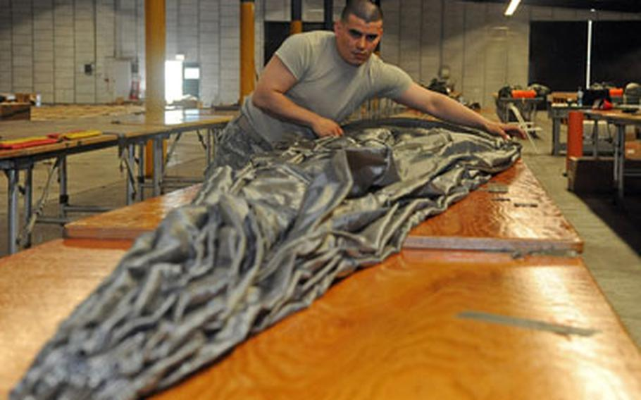 Sgt. Oscar Osorio, a parachute rigger with the 5th Quartermaster Detachment, 21st Theater Sustainment Command, packs a new MC-6 parachute at a warehouse on Rhine Ordnance Barracks in Kaiserslautern, Germany.