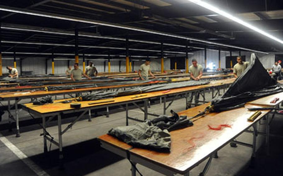 Parachute riggers with the 5th Quartermaster Detachment, 21st Theater Sustainment Command, pack new MC-6 parachutes at a warehouse on Rhine Ordnance Barracks in Kaiserslautern, Germany.