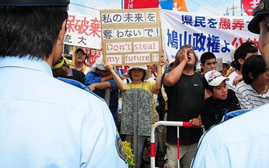 """Demonstrators gather outside the Futenma Elementary School No. 2, chanting anti-military base slogans, while inside some protesters shouted """"Shame! Shame!"""" to Prime Minister Yukio Hatoyama during a Town Hall meeting in which he declared that U.S. Marine units would not be transferred off Okinawa."""