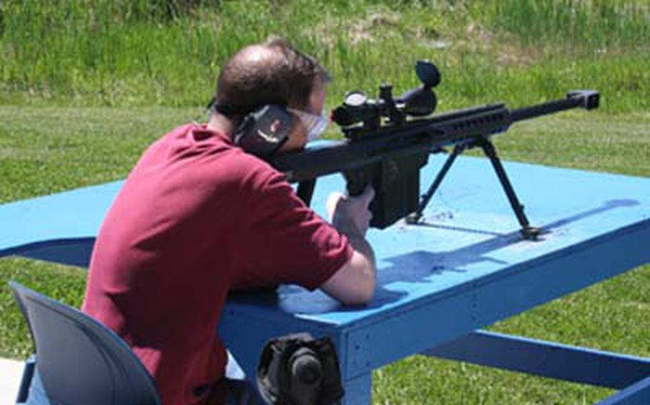 Stars and Stripes copy editor Thomas Ruyle fires the M107 .50-caliber sniper rifle, which has such a strong recoil that it will rattle your teeth, he said.