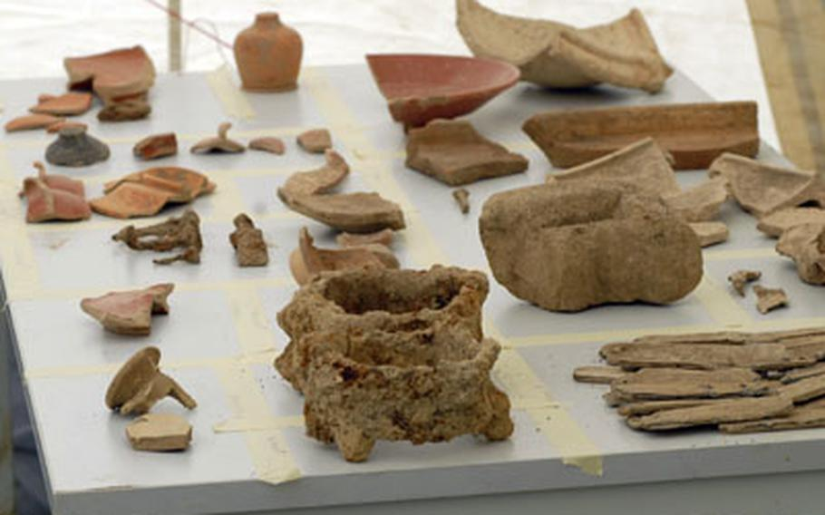 Artifacts from around the first century A.D. sit on display near the excavation site of what German archaeologists say was a Roman farming settlement.