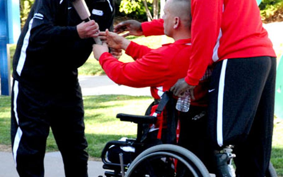 Army Sgt. Robert Price, who lost part of his right leg in Iraq, passes the torch to former Lance Cpl. Charles Sketch, who is a blind double-amputee, with the help of Gunnery Sgt. Marcus Wilson, during the opening ceremony Monday at the inaugural Warrior Games for wounded servicemembers. The torch was passed from service to service.