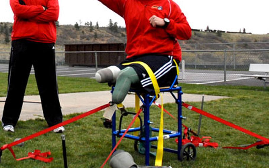 Former Marine Sgt. Bradley Walker practices shot put last week at the United States Air Force Academy in Colorado Springs, Colo., as his coach, also a former Marine sergeant, Eric Bildstein, looks on. Walker, a double-amputee, is also participating in hand cycling and sitting volleyball during the inaugural Warrior Games.