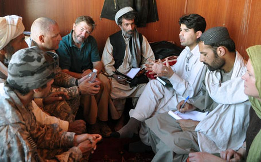 Ghulam Faruq Hamayoon, sub-governor of Logar province's Kharwar district (sitting under the jacket), meets with soldiers and reconstruction officials in the cramped trailer that serves as his headquarters. Hamayoon, who was hired after the last sub-governor simply left and never returned, has no staff and says he feels abandoned by his government.