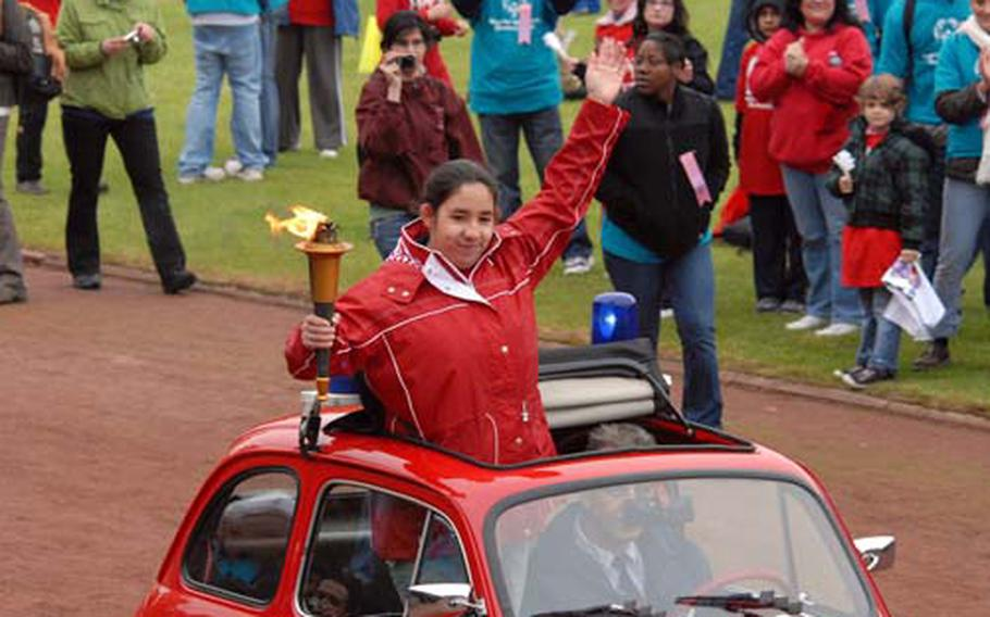 Brenda Guzman waves to the crown as she brings the Special Olympics torch into the stadium during the opening ceremony.