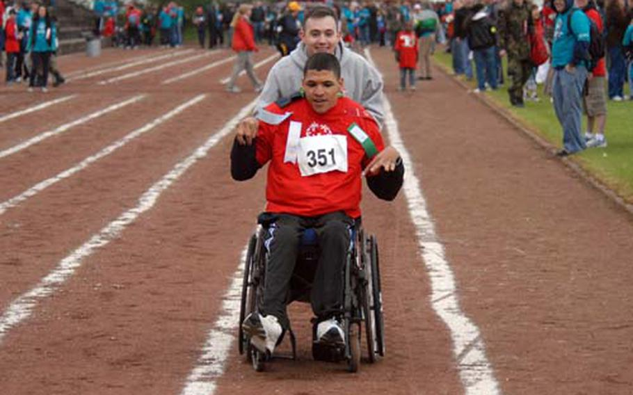 Special Olympian Etienne Glaster races down the track with buddy Andrew Medley.
