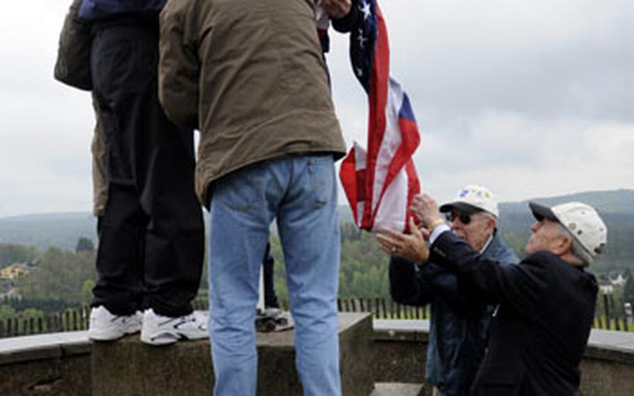 """Retired servicemembers of the 100th Infantry Division and family members raise the American flag over the Citadel of Bitche, France, on May 7. The 100th Division is now known as the """"Sons of Bitche"""" for its efforts in liberating the town from the Nazis."""