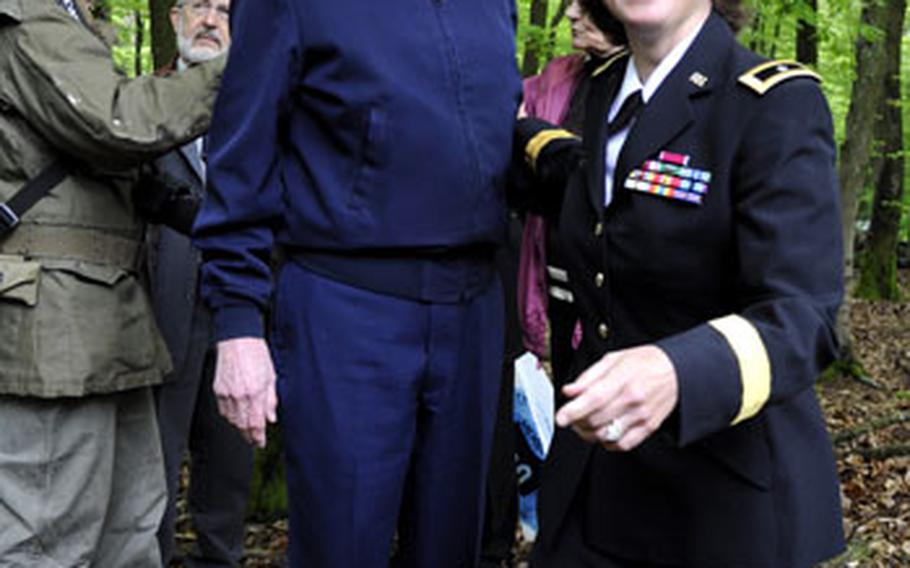 Retired Army Col. John E. Halver helps the Army's 100th Division commanding general, Brig. Gen. Patricia Heritsch, into a foxhole he fought in during a battle with Nazi forces on a hill near Lemberg, Germany on Victory in Europe Day on Saturday. Halver was a second lieutenant platoon commander when he fought there in 1945.
