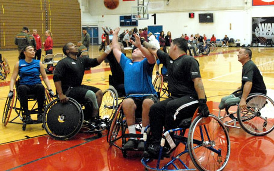 Air Force Staff Sgt. Richard Pollock, in blue in the center, reaches for a rebound from his teammates shot in a wheelchair basketball game Wednesday night against Army in the inaugural Warrior Games for wounded servicemembers. The Air Force ended up taking bronze in the competition. The Gold Medal game is Thursday night.