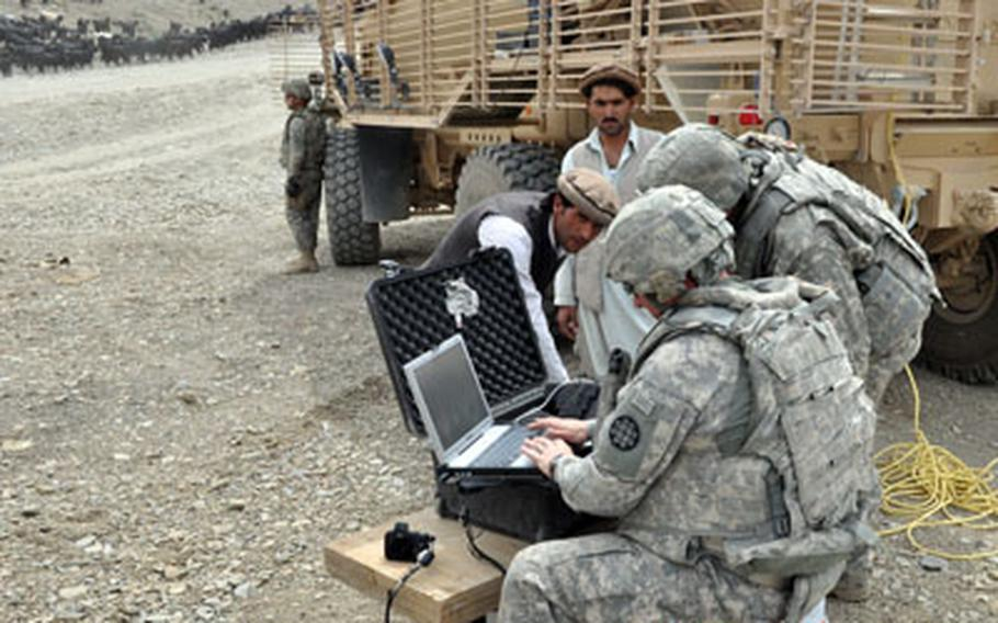 Soldiers from a route clearance unit enroll passers-by in a database system after setting up a checkpoint along Route Alaska.