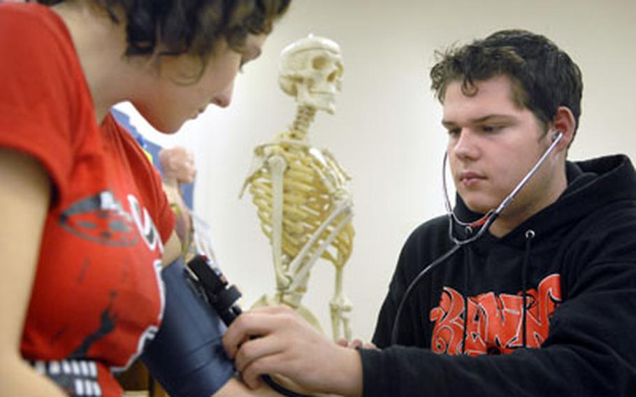 Nikolas Siegmund checks Kaitlin Hines' blood pressure during health science class in January at Ramstein High School.