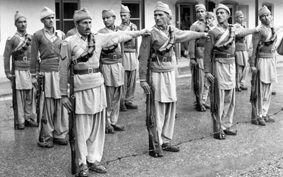 Troops shape up in front of their barracks for an inspection.